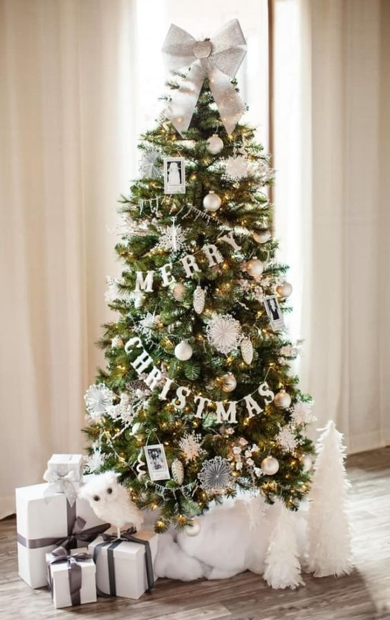 a very glam and chic Christmas tree with lights, letter banners, white and silver ornaments, a white bow and cotton under the tree