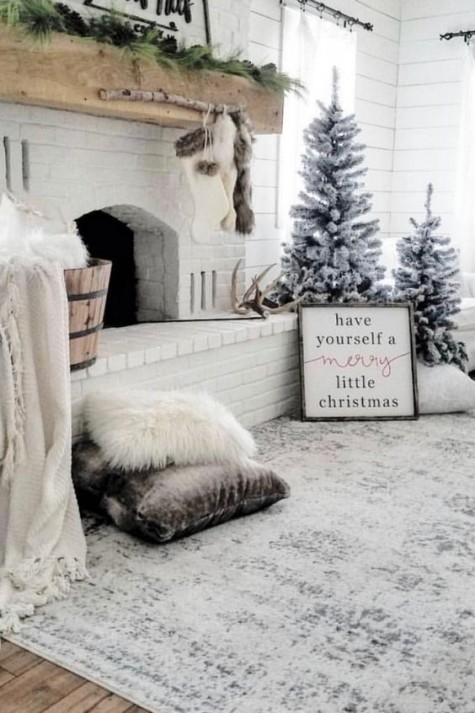 a beautiful fireplace with velvet and faux fur pillows, snowy Christmas trees and some fur stockings for a winter wonderland feel