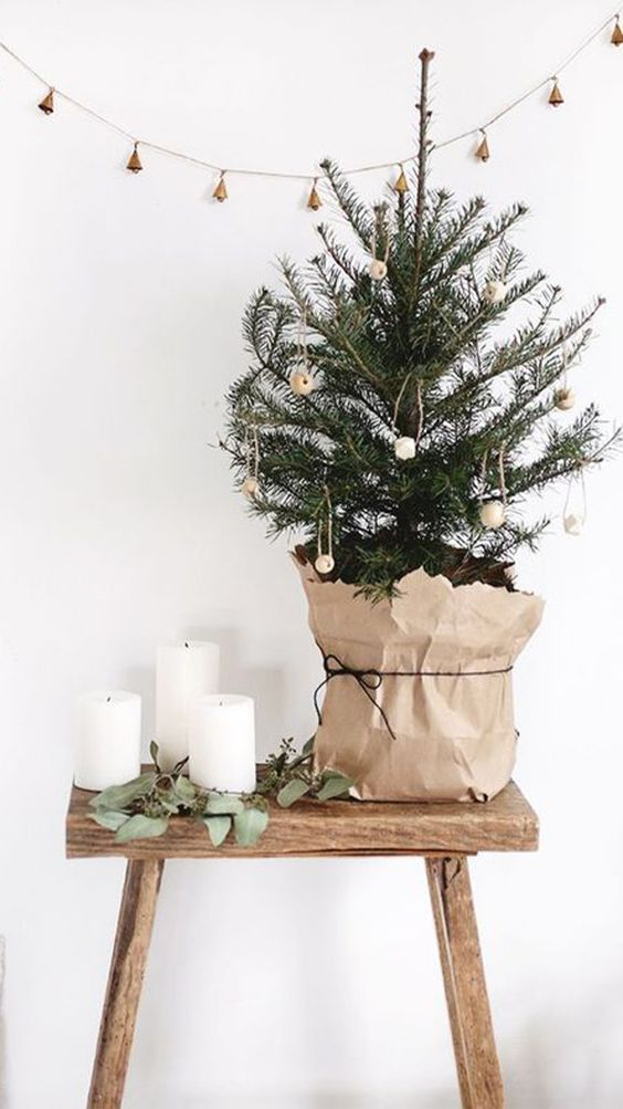 a small Nordic Christmas tree with wooden bead ornaments and a kraft paper cover is a pretty and nice idea with a natural feel