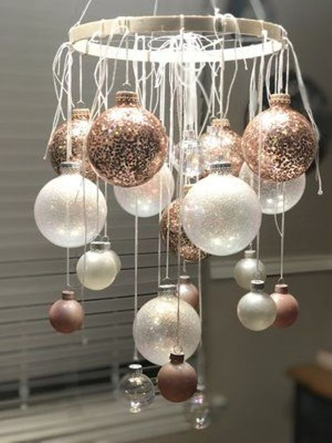 a Christmas ornament chandelier of an embroidery hoop, copper, white and sheer ornaments of various sizes