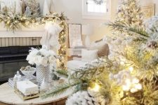 13 a dreamy winter wonderland living room with a flocked garland with lights, mini trees, a flocked Christmas tree, pinecones and berries