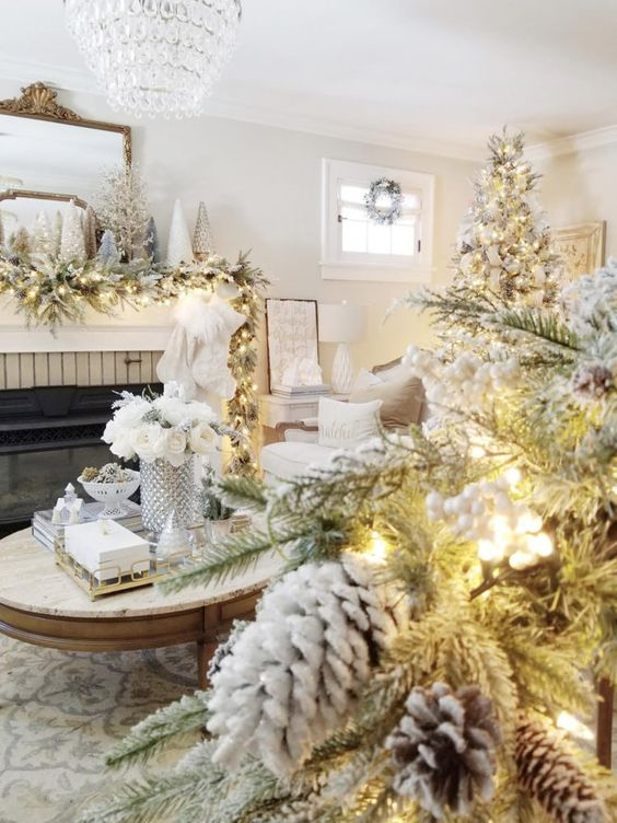 a dreamy winter wonderland living room with a flocked garland with lights, mini trees, a flocked Christmas tree, pinecones and berries