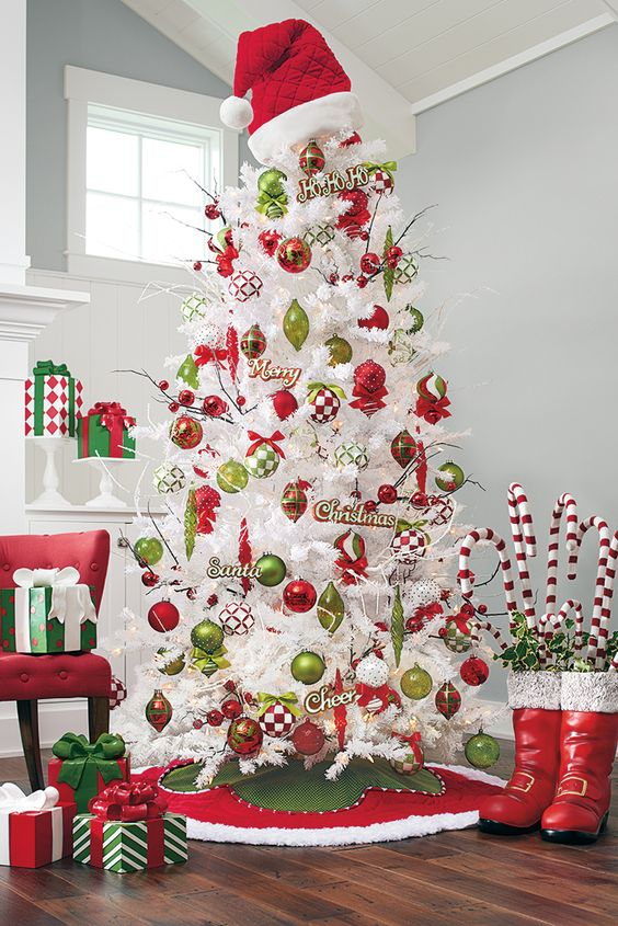 a whimsical white Christmas tree decorated with green and red ornaments of various looks and a red Santa hat on top