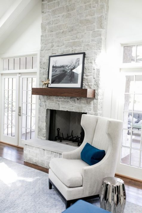 a white space made cozier with a whitewashed stone fireplace, a dark stained mantel and a metallic side table