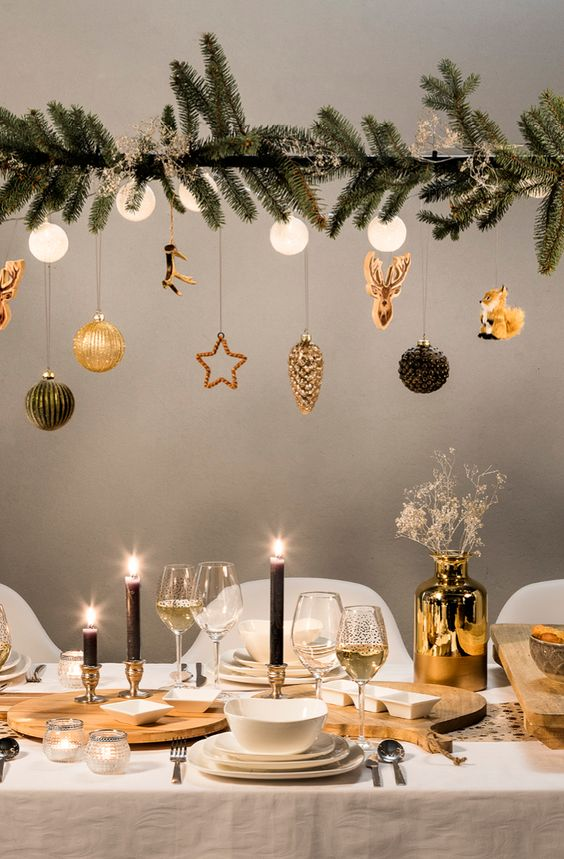 a chic Christmas tablescape and an overhead decoration of fir branches, lights, chic gold and black ornaments hanging over the table