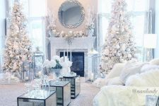 14 a frozen living room with white Christmas trees with silver and white ornaments, white faux fur on the furniture and chic frozne mantel decor