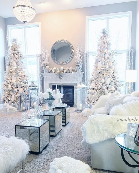 a frozen living room with white Christmas trees with silver and white ornaments, white faux fur on the furniture and chic frozne mantel decor