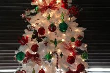 14 a white Christmas tree with lights, red and green ornaments, candy canes and a red star topper is a bold and cool piece to rock
