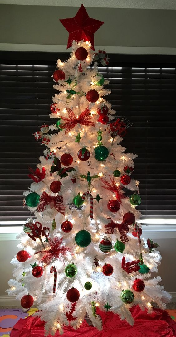 a white Christmas tree with lights, red and green ornaments, candy canes and a red star topper is a bold and cool piece to rock