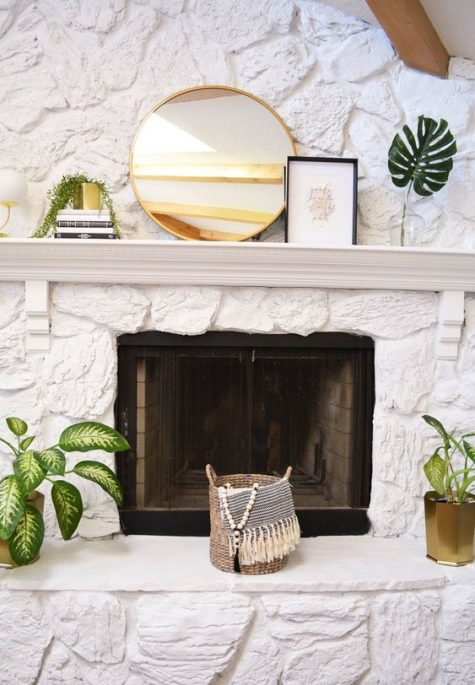a white stone fireplace with a mantel with a mirror and artworks, potted plants around and a basket with a blanket