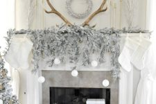 15 a gorgeous winter wonderland space with frozen fir branches, a flocked Christmas tree, wreaths and snowballs over the fireplace