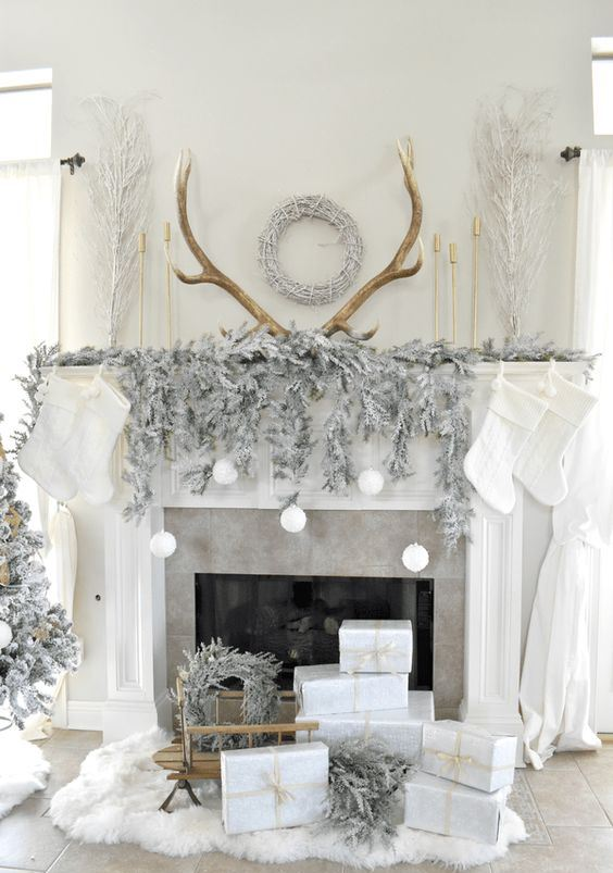 a gorgeous winter wonderland space with frozen fir branches, a flocked Christmas tree, wreaths and snowballs over the fireplace