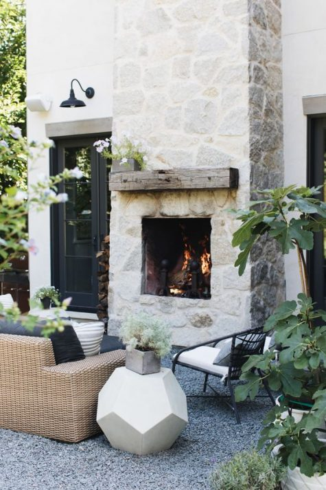 a whitewashed stone fireplace with a rough wooden mantel is a centerpiece of this chic outdoor space