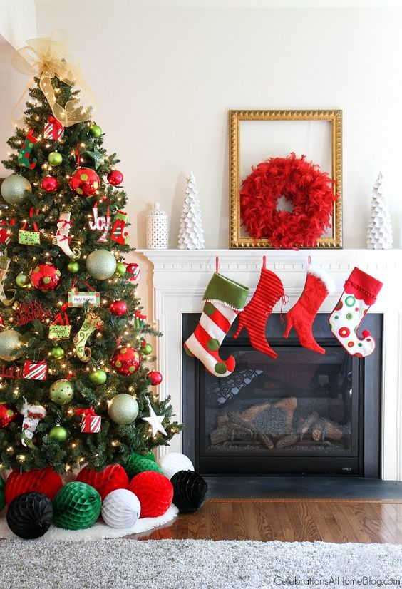 bright and fun Christmas tree decor with oversized and whimsical ornaments, lights, stars and stockings, bright stockings and a red wreath