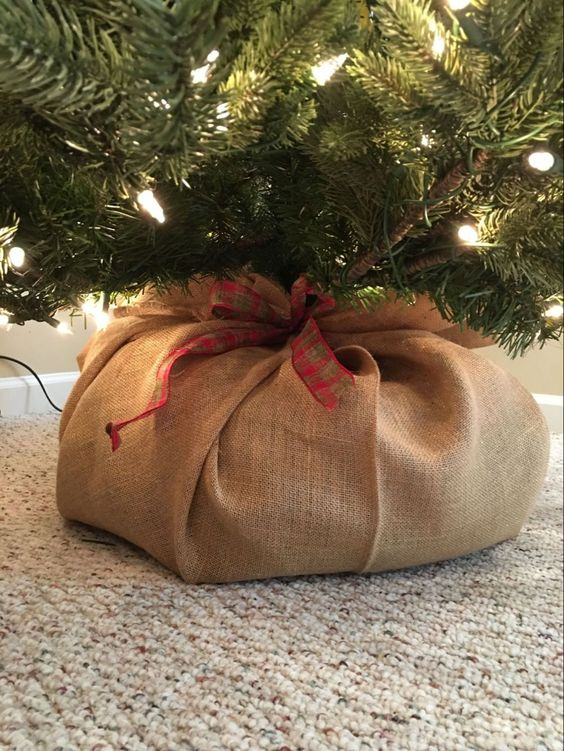 cover your Christmas tree with burlap and a add a plaid ribbon bow to make it look a bit rustic and very cozy