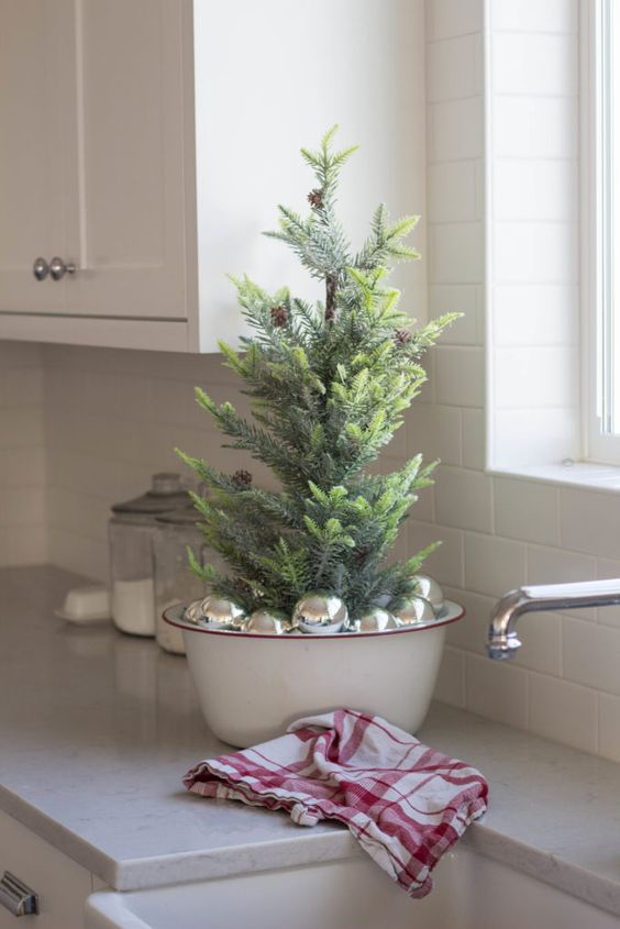 a bowl with silver ornaments and a small Christmas tree with pinecones is a lovely idea for simple and minimal holiday decor