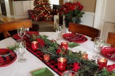 16 a cozy Christmas tablescape with a plaid linens, red plates and candleholders, berries and green plates plus fir branches is chic