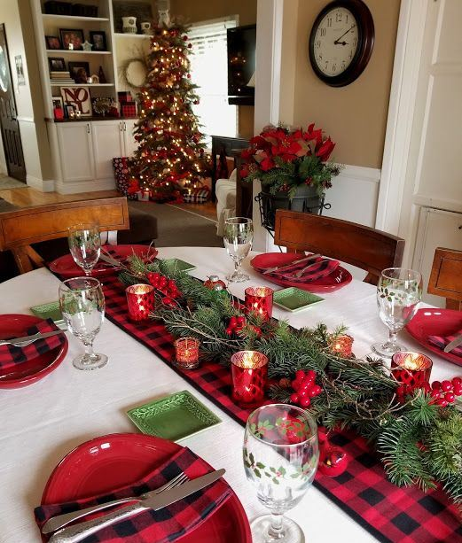 a cozy Christmas tablescape with a plaid linens, red plates and candleholders, berries and green plates plus fir branches is chic