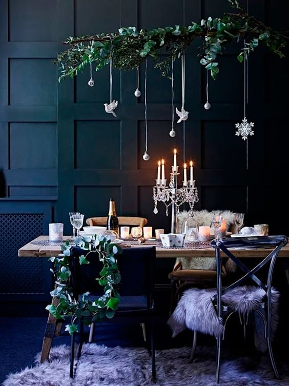 a lovely Christmas tablescape with a refined candelabra and a fresh greenery installation with elegant white ornaments
