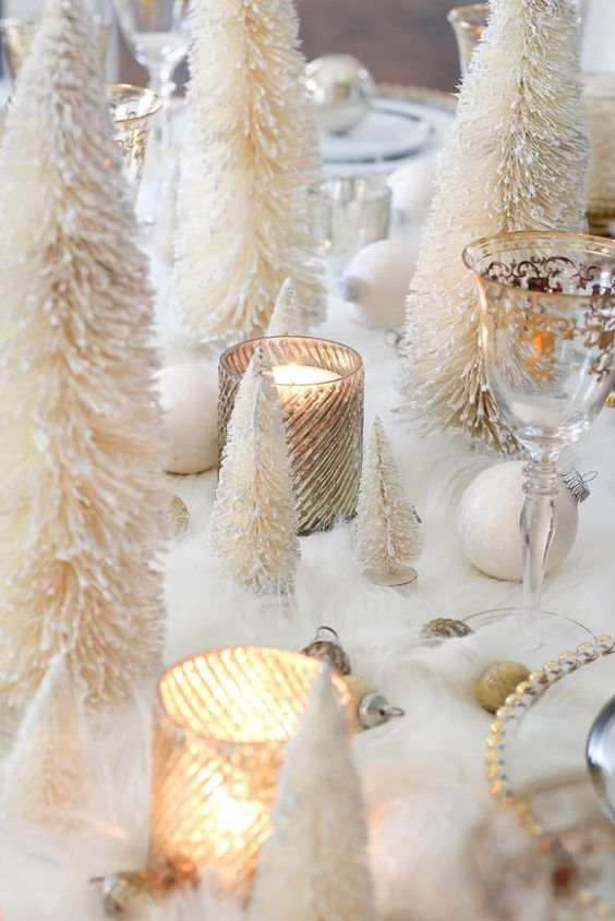 a lovely winter wonderland tablescape with faux fur, white and gold ornaments, candles in glass candleholders, mini tinsel Christmas tres