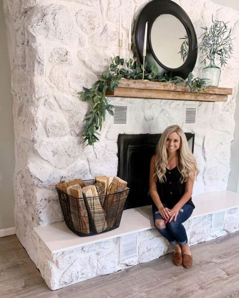 a whitewashed stone fireplace with a wooden mantel, a metal basket with firewood, greenery and candles
