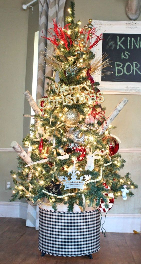 a bright rustic Christmas tree with lights, branches, plaid and polka dot ornaments and metallic ones, too plus a plaid cover