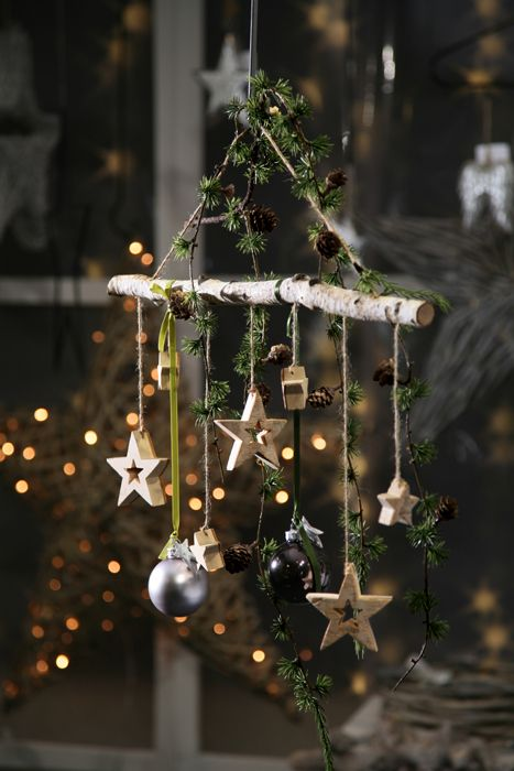 a natural Christmas decoration of a stick, greenery, pinecones, ornaments and wooden stars is lovely