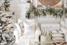 17 a shabby chic winter wonderland living room with a flocked fir garland, a flocked Christmas tree with lights and branches in a bucket