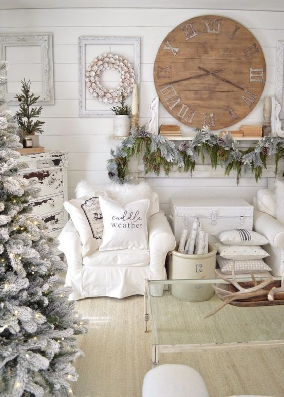 a shabby chic winter wonderland living room with a flocked fir garland, a flocked Christmas tree with lights and branches in a bucket