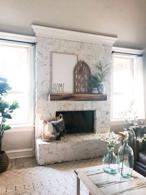 a whitewashed brick fireplace with a wooden mantel, greenery in vases and art plus a basket with blankets