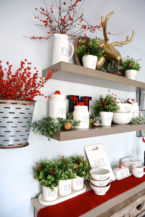 beautiful farmhouse Christmas decor with a red runner, faux greenery and berries, bells and a gold deer head on top