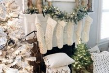 18 a snowy Christmas tree with lights, faux fur stockings and a chunky knit throw, candles in wooden candleholders for a winter wonderland feel