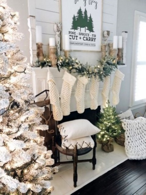 a snowy Christmas tree with lights, faux fur stockings and a chunky knit throw, candles in wooden candleholders for a winter wonderland feel