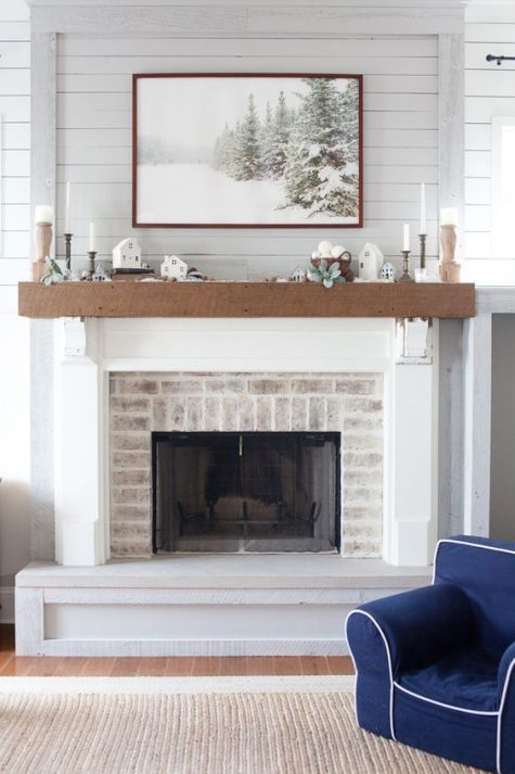 a whitewashed brick fireplace with a stained wooden mantel, with winter decor and a beautiful artwork over the space