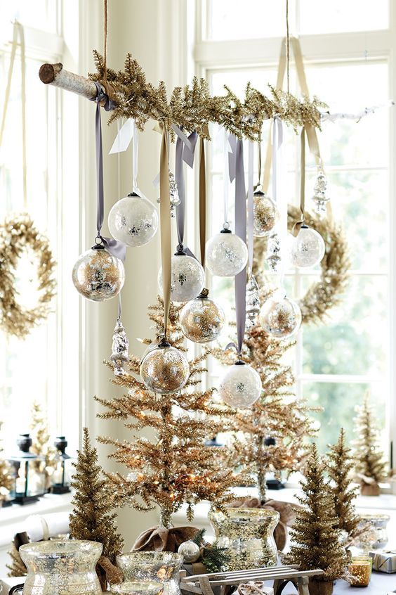 an overhead Christmas installation with gold fir branches, white and gold ornaments and lots of gold Christmas trees