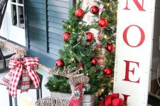 18 beautiful rustic Christmas decor with a tree in a bucket, greenery branches with red ornaments, a vine deer and a box with red bows