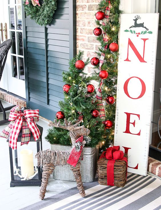 beautiful rustic Christmas decor with a tree in a bucket, greenery branches with red ornaments, a vine deer and a box with red bows