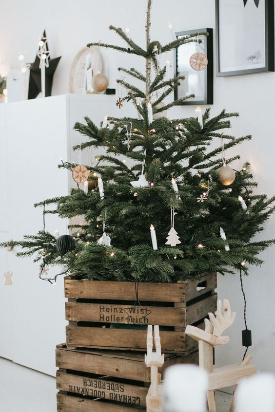 a Nordic Christmas tree with lights, porcelain and wooden ornaments and with old crates cover the tree base