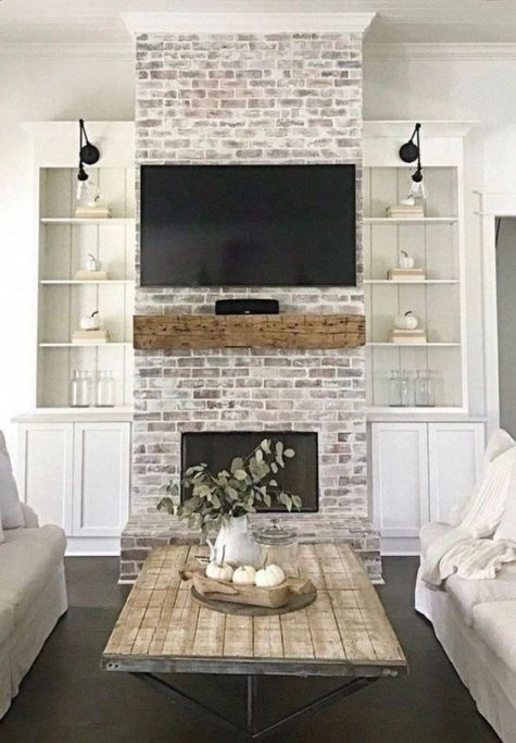 a whitewashed brick fireplace with a rough wooden mantel makes the farmhouse living room cozier