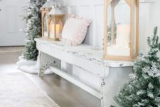 19 a winter wonderland entryway with mini flocked Christmas trees, wooden lanterns, a shabby chic bench with a pink pillow