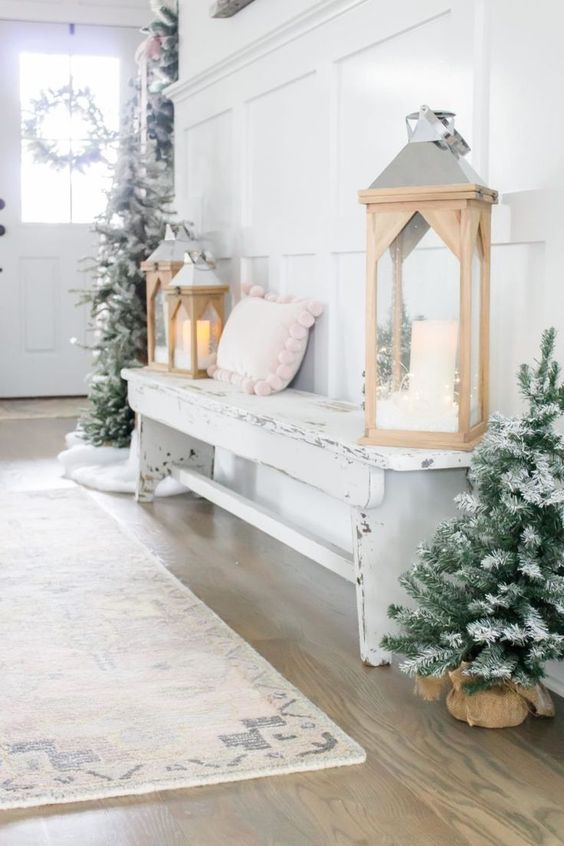 a winter wonderland entryway with mini flocked Christmas trees, wooden lanterns, a shabby chic bench with a pink pillow