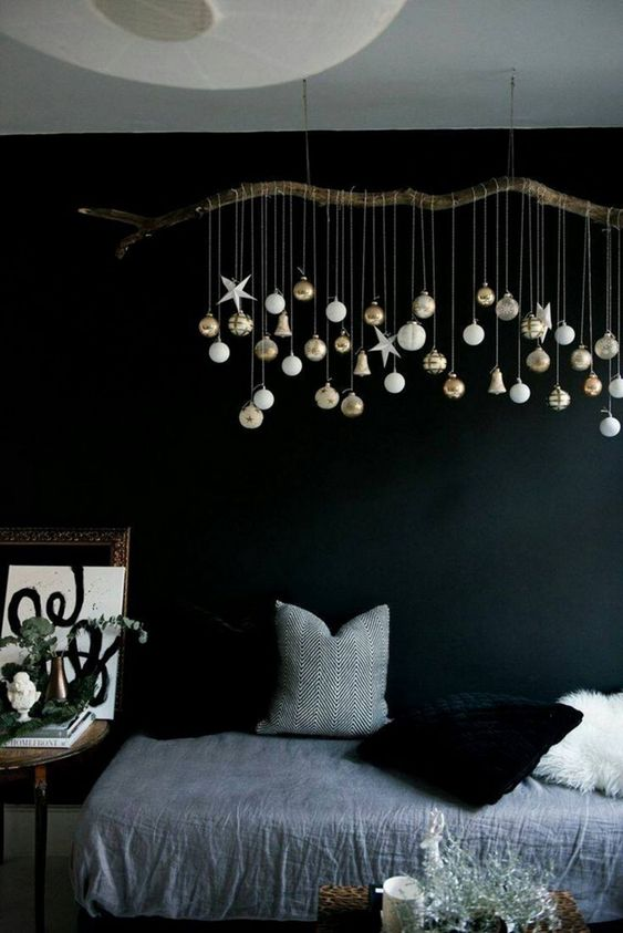 an overhead Christmas installation of a branch with white and gold ornaments is a great idea for every kind of space