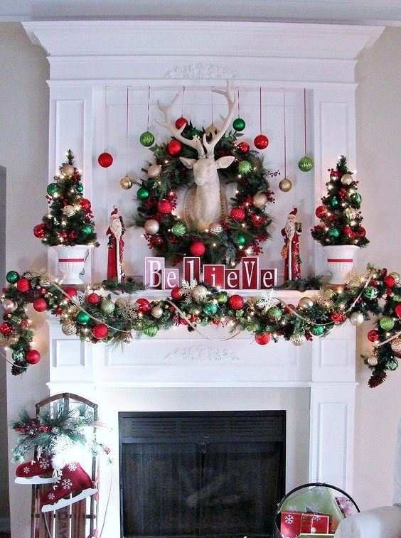 cozy and chic Christmas decor with red and green ornament garlands and a wreath, mini trees and lights, a deer head and red skates
