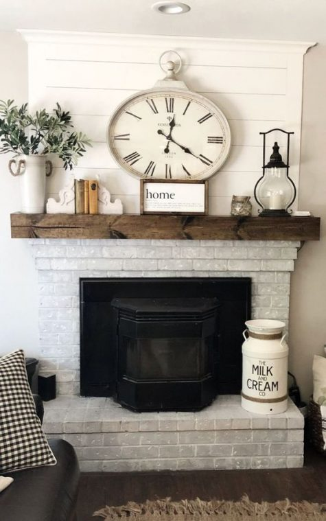 a whitewashed brick fireplace with a dark stained mantel, a milk churn, candle lanterns and a vintage clock is very cool