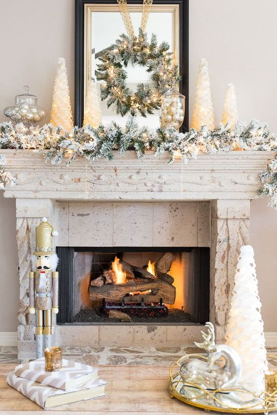a winter wonderland mantel with a flocked Christmas garland, a wreath with lights, mini Christmas trees, vintage decor and silver ornaments in a jar
