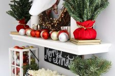 20 elegant rustic Christmas decor with fir branches, white roses, a candle lantern with gold and red ornaments and the same ornaments on the shelf