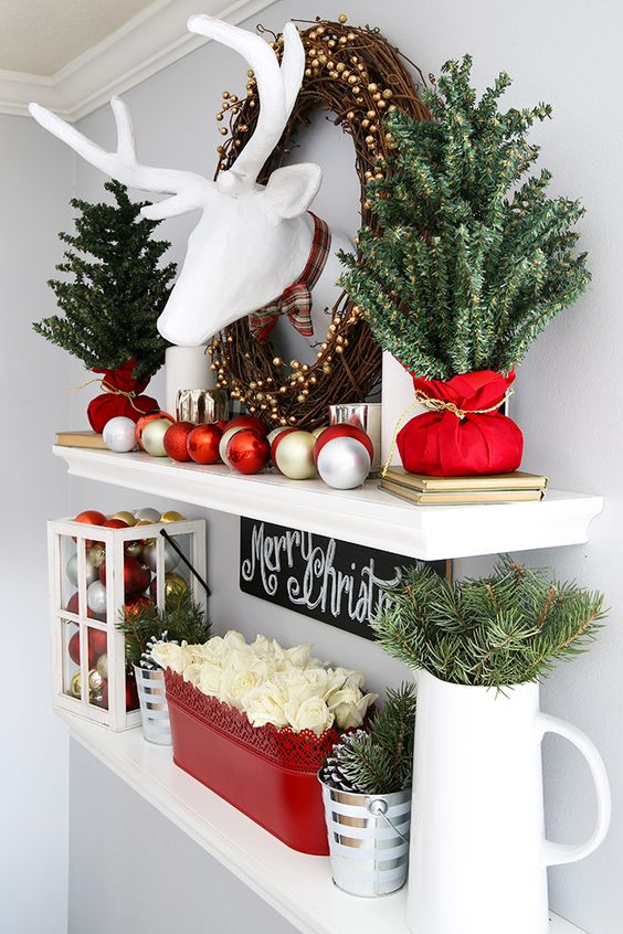 elegant rustic Christmas decor with fir branches, white roses, a candle lantern with gold and red ornaments and the same ornaments on the shelf
