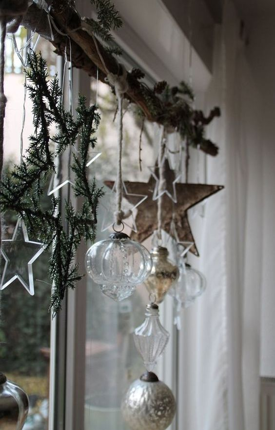 Nordic Christmas window decor with fir branches, a wooden star, sheer and silver ornaments, sheer stars and lights