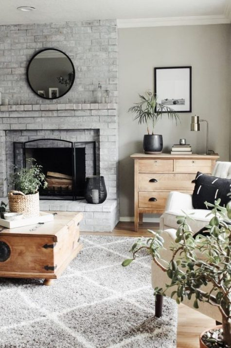 a neutral farmhouse living room with a whitewashed brick fireplace, wooden and neutral upholstered furniture and potted plants