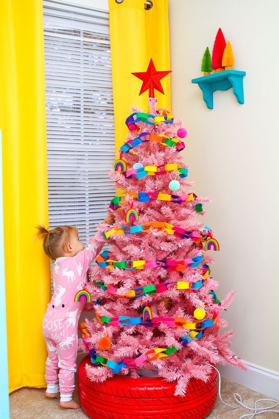 a pink Christmas tree decorated with colorful chains and with a red tire as a cover for the base of the tree